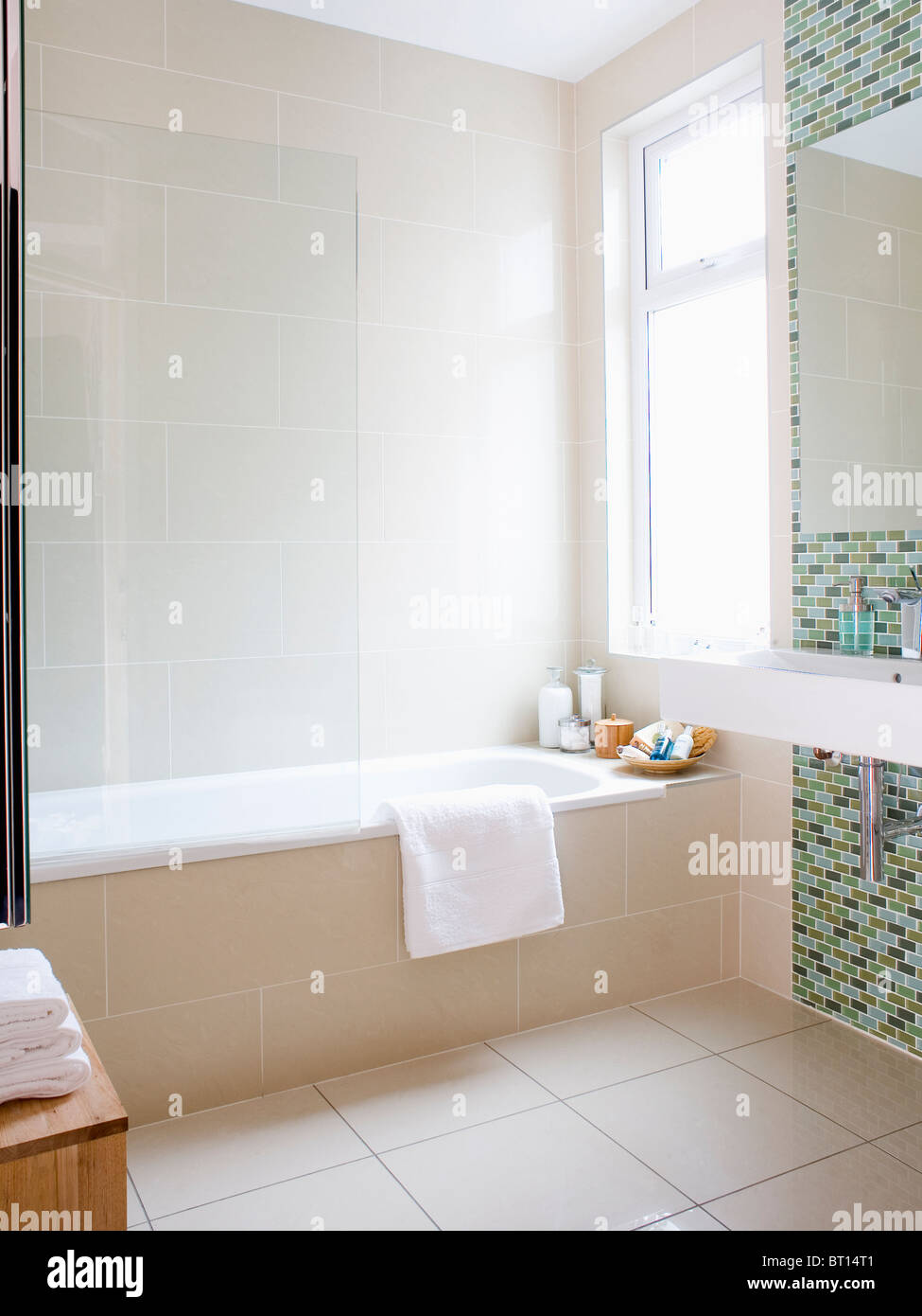 Glass shower screen on bath in modern cream tiled bathroom Stock ...