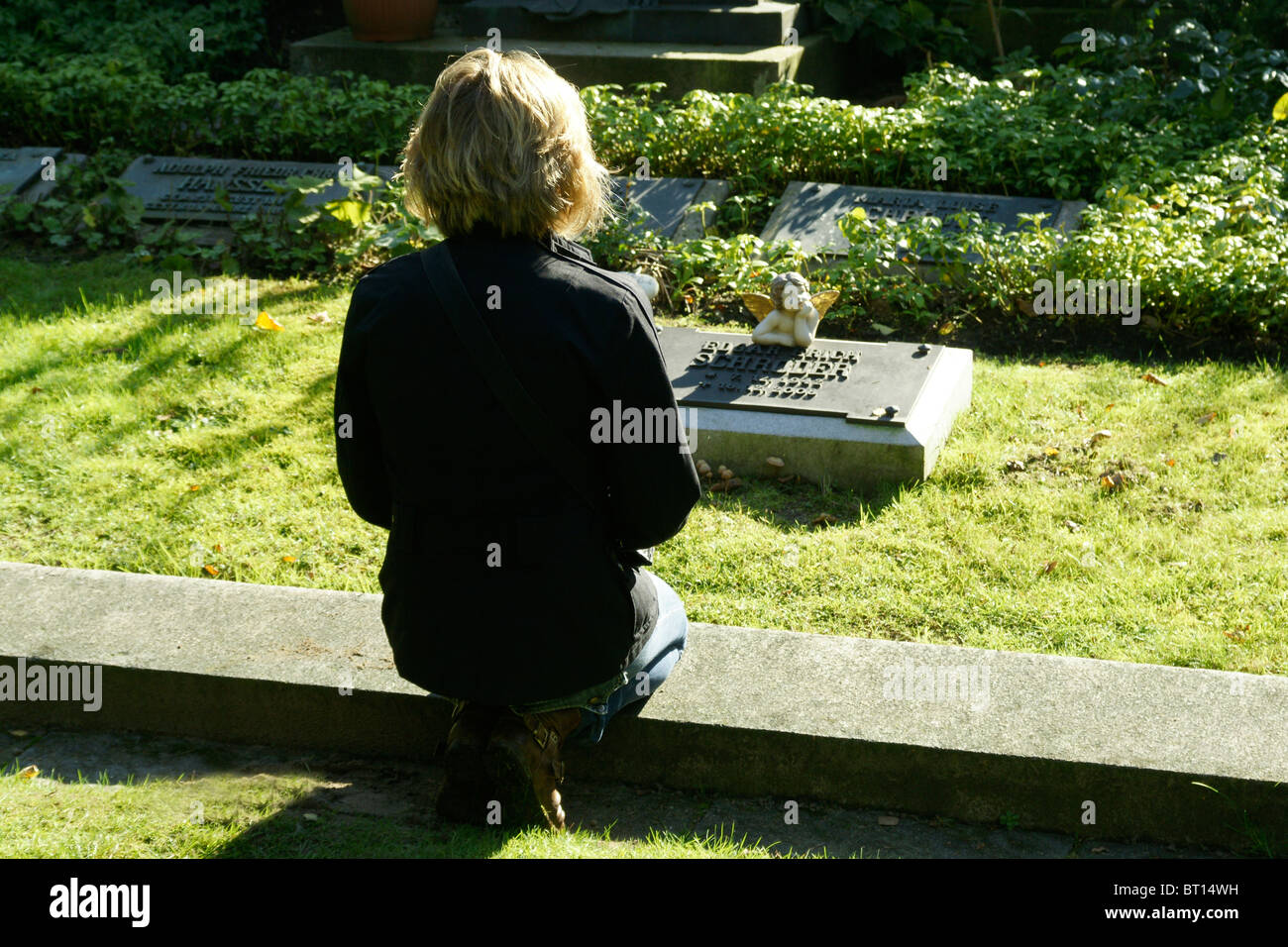 Woman at a cemetery - Stock Image