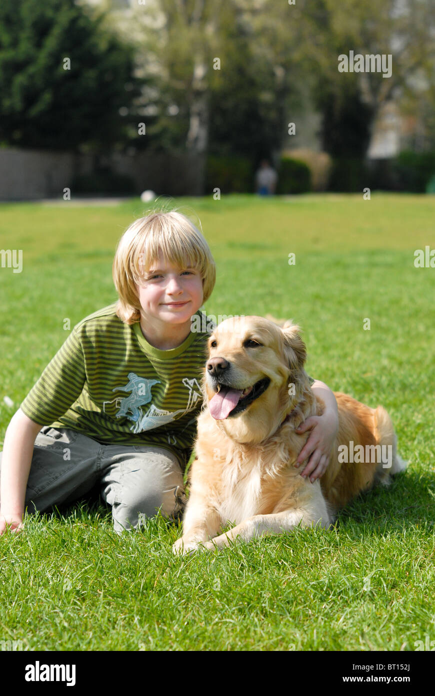 Blond-haired boy sitting on the grass in a park hugging his Golden Retriever pet dog on a hot sunny day - Stock Image