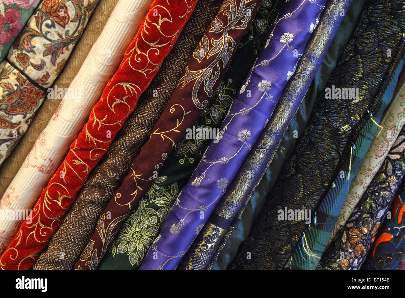 Colorful and elegant bolts of velvet and silk fabric cloth in seamstress shop - Stock Image