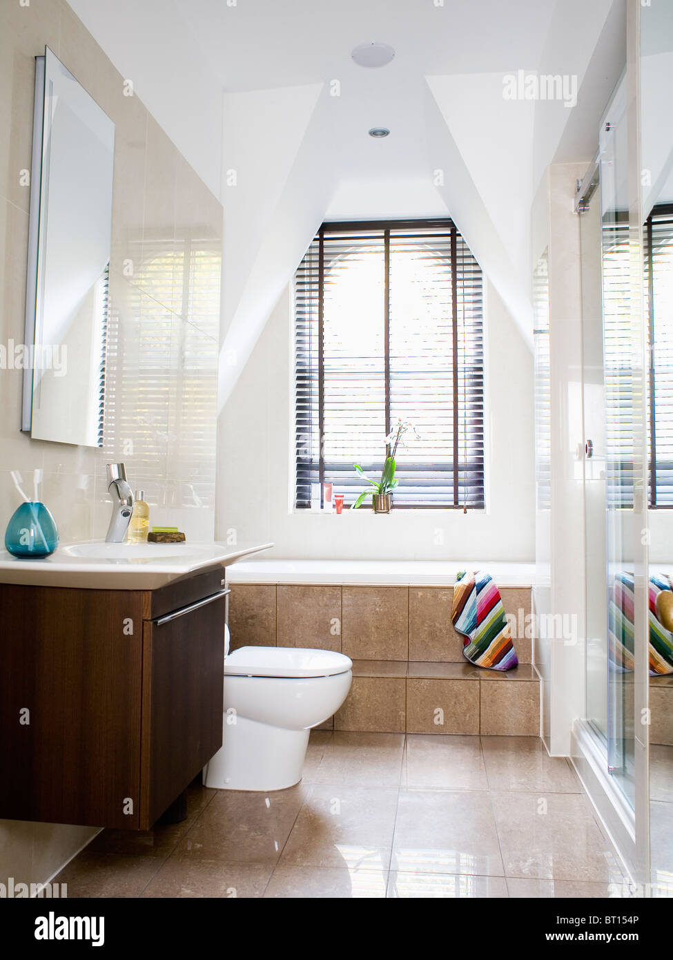 Step up to bath below window with black Venetian blind in modern ...