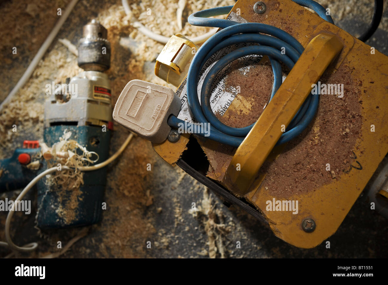 dangerous and messy workshop with unsafe power tools, such as a damaged drill and transformer  which creates a fire - Stock Image