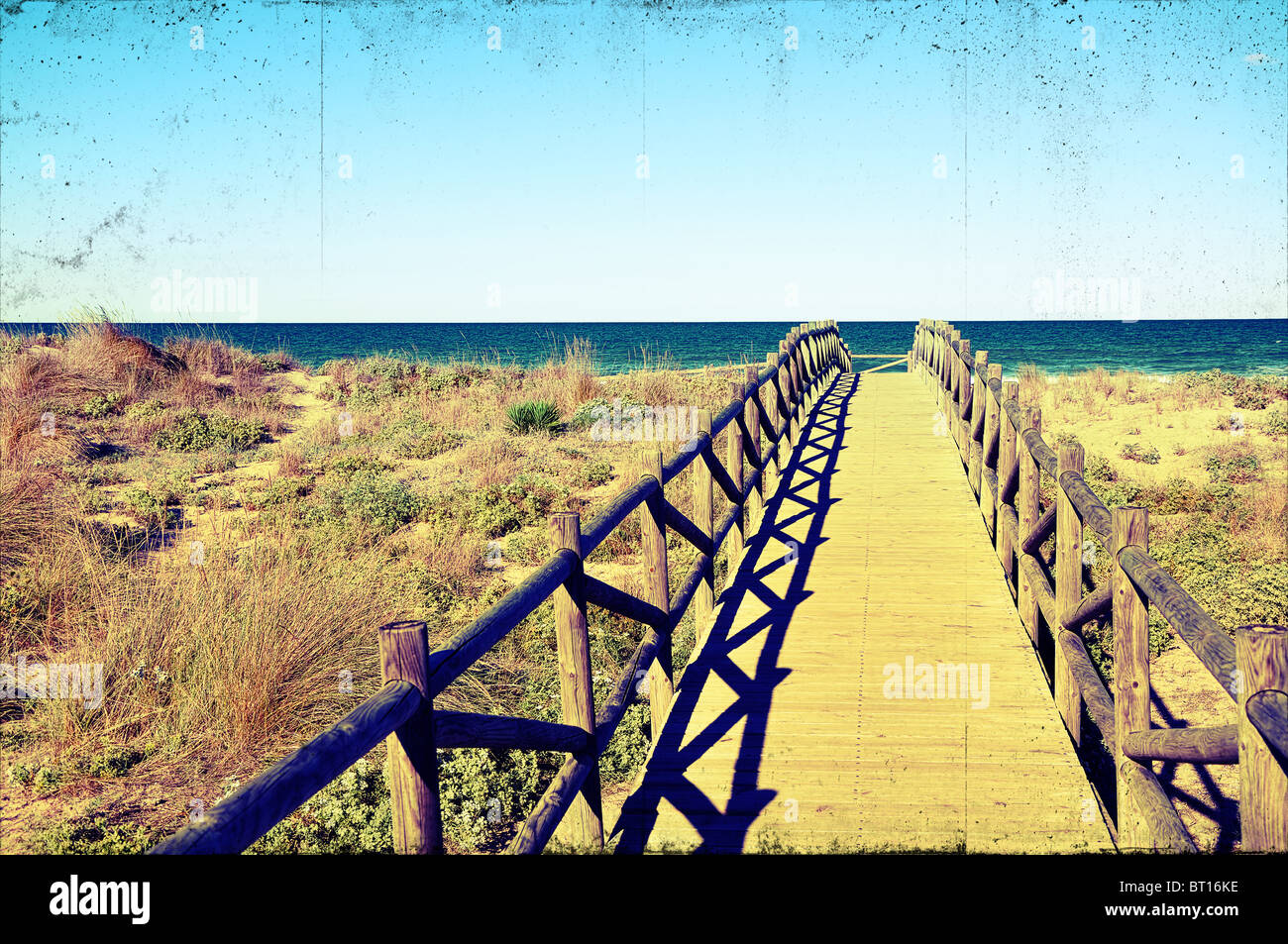 wooden bridge over beach dunes with a cross process and vigneting effect to look grungy and old - Stock Image