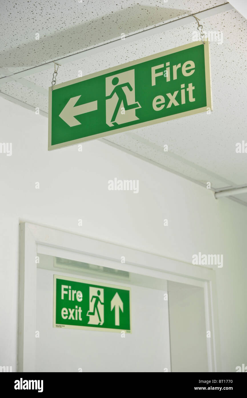 Fire safety exit signs placed correctly showing exit for escape - Stock Image