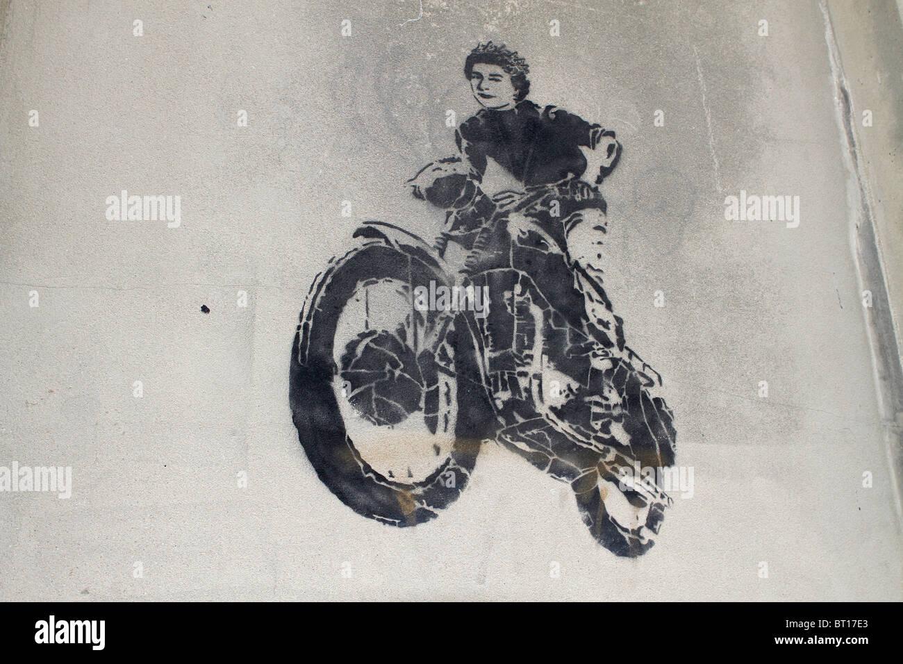 McQueen stencil greffiti, Queen Elizabeth 2nd motorbike jump from the great escape movie, street art London, UK - Stock Image