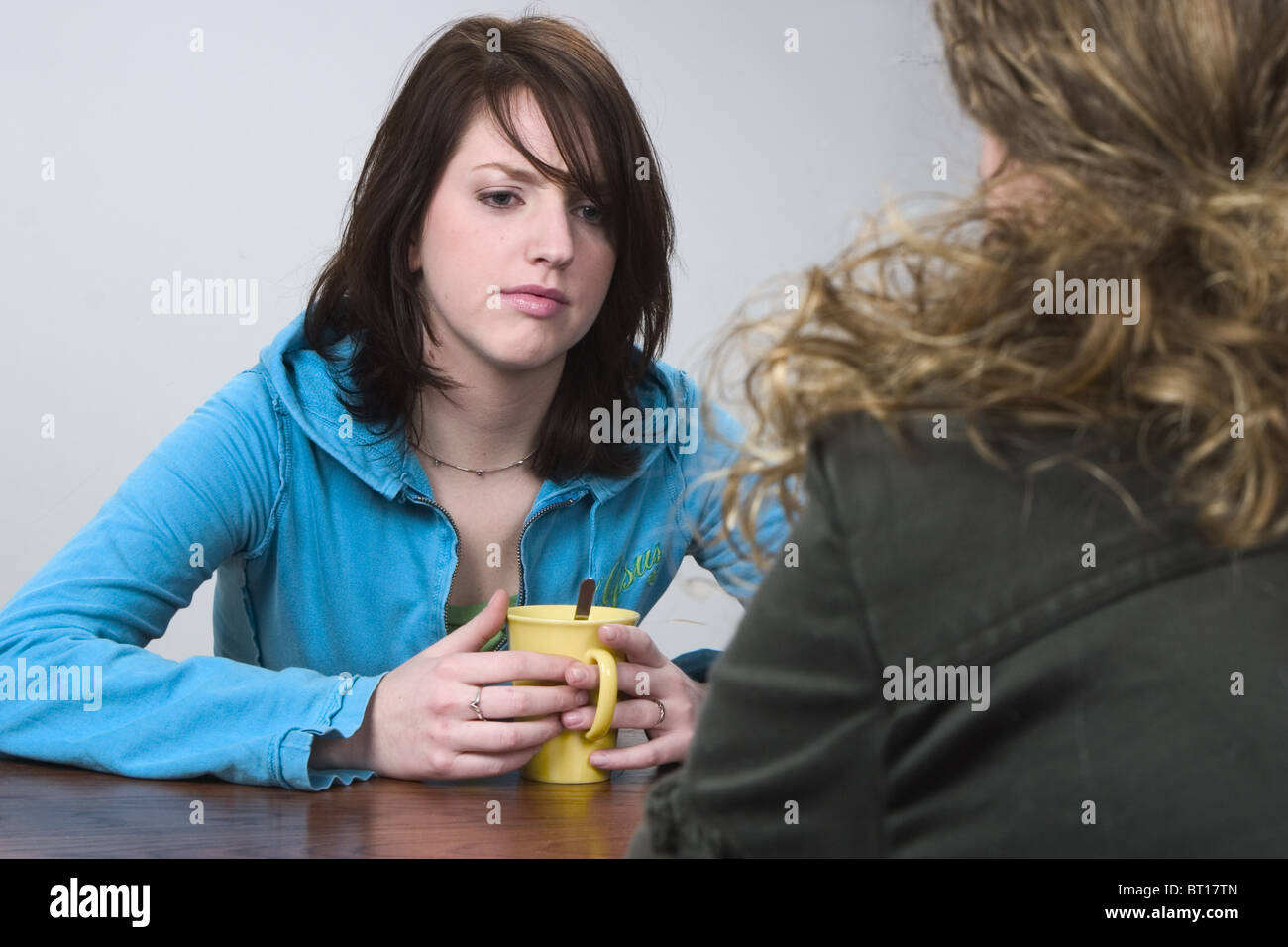 Two introspective women drinking coffee in silence - Stock Image