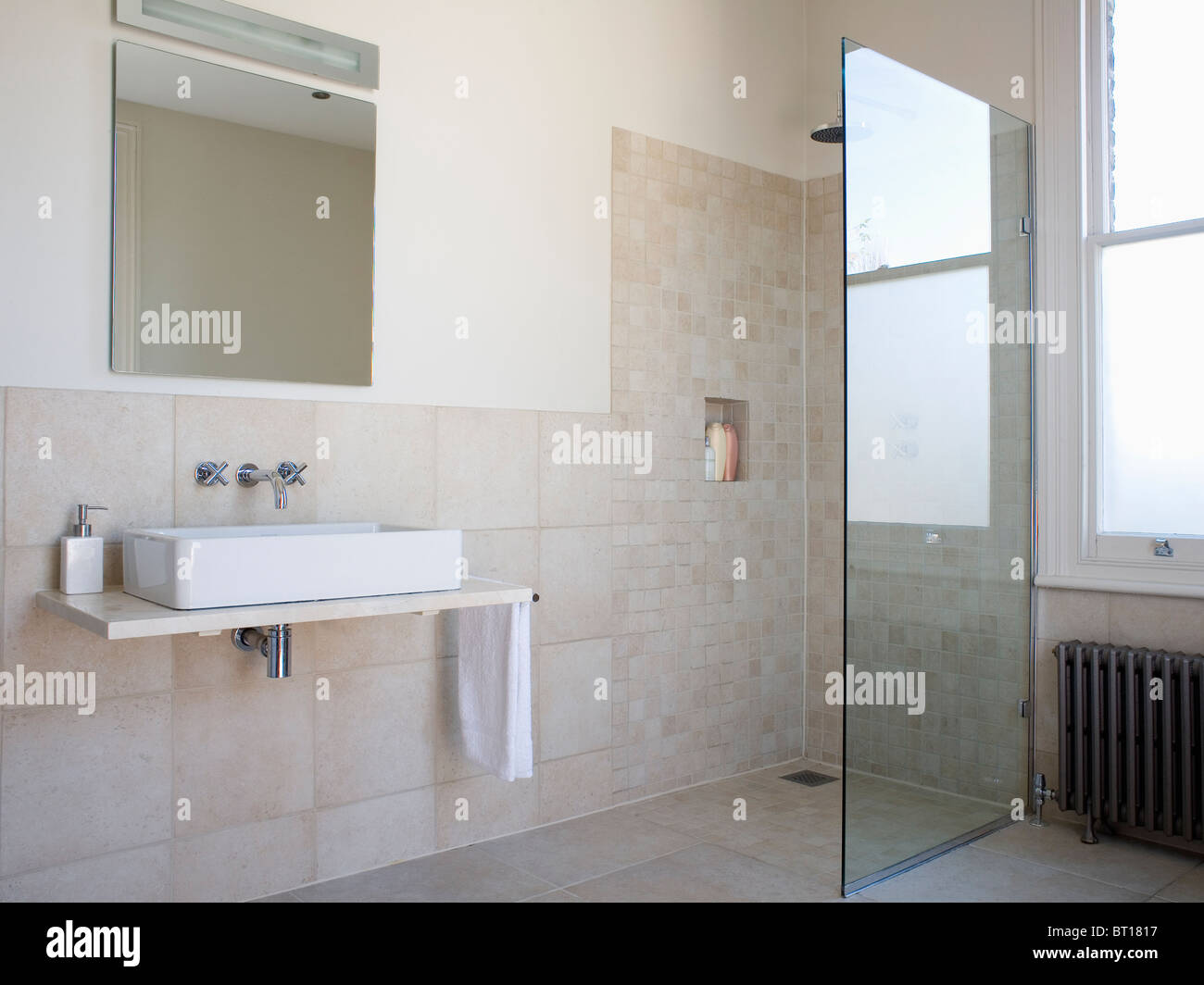 Walk-in wet room with glass shower wall in modern beige tiled Stock ...