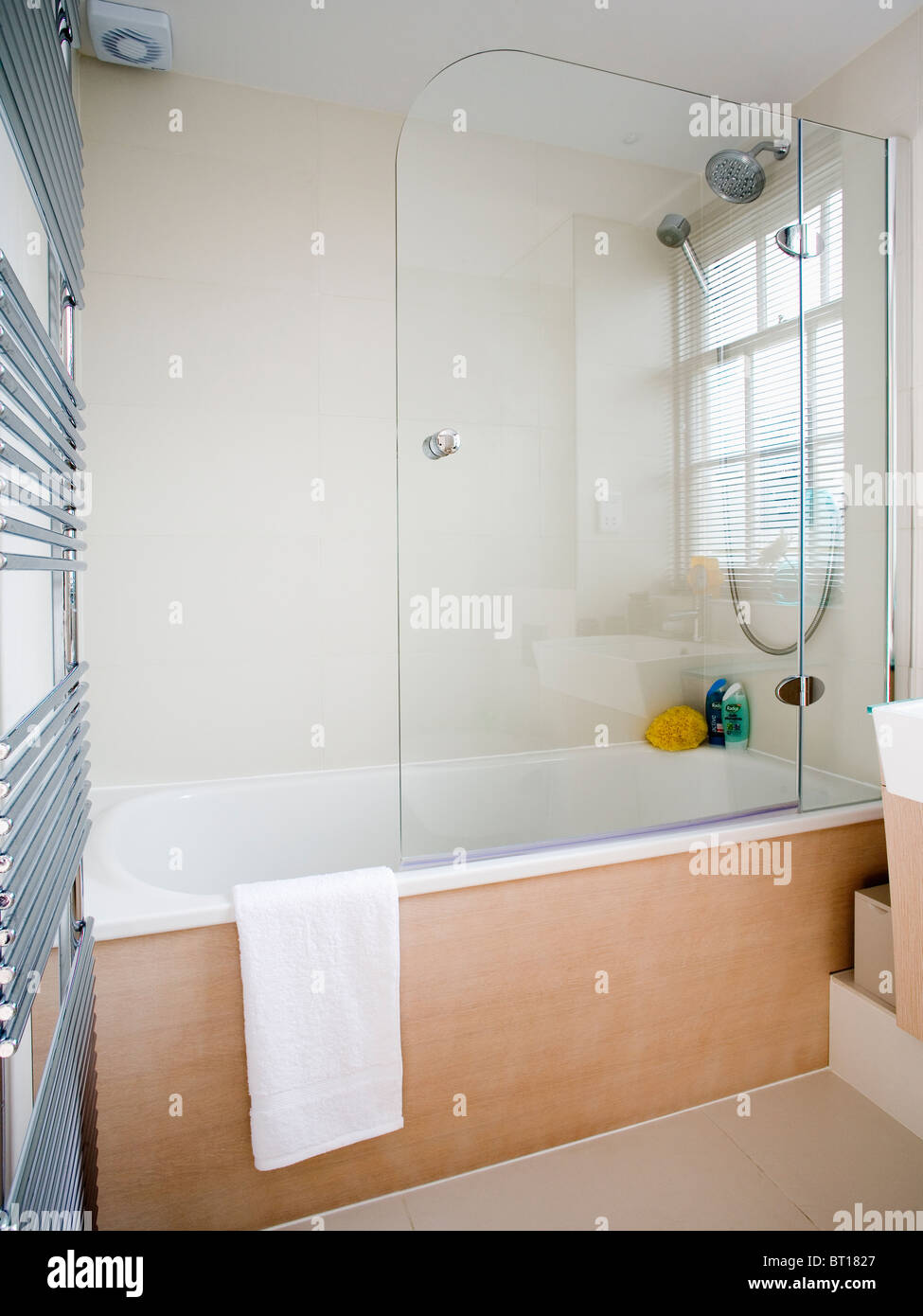 Glass shower screen on bath with pale wood panel in modern white ...