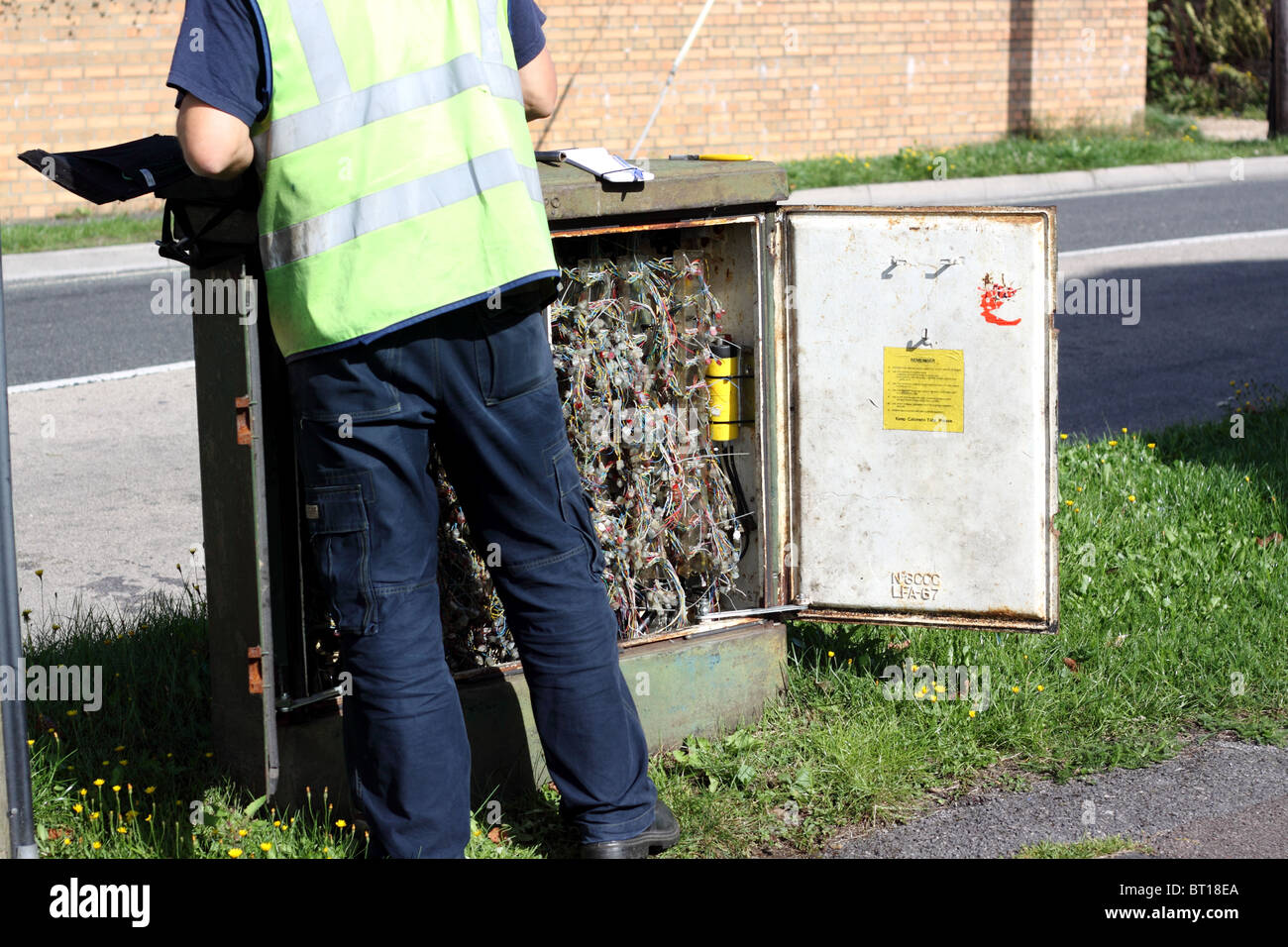 a british telecom telephone engineer examining a junction box or cabinet  full of cables  -