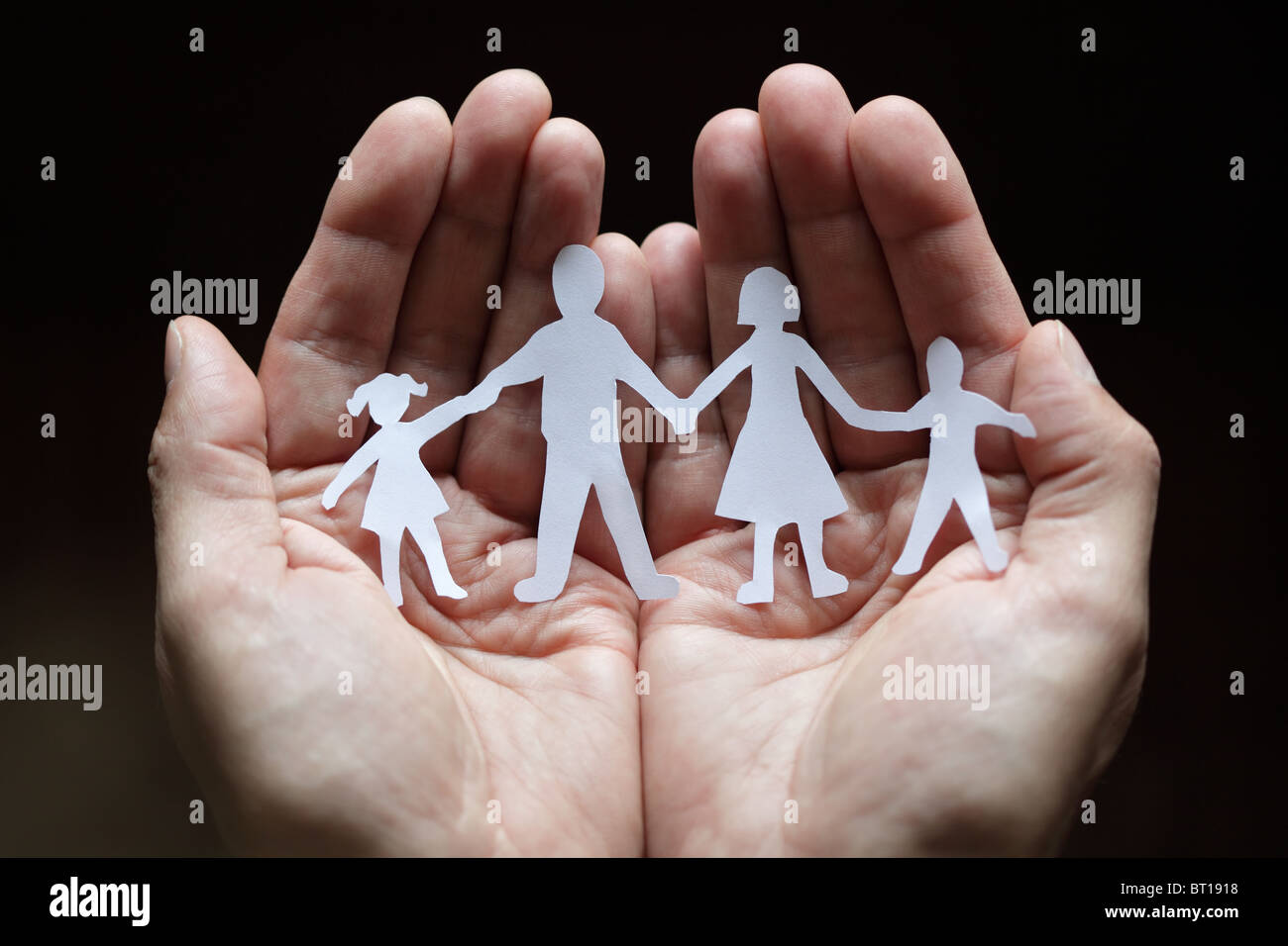 Paper chain family protected in cupped hands - Stock Image
