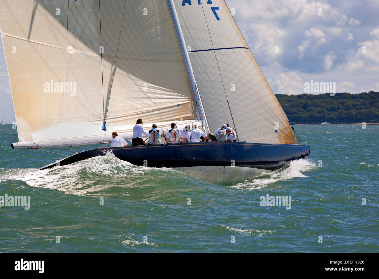 modern racing yacht speeding through the water with co-operation and teamwork of the crew - Stock Image