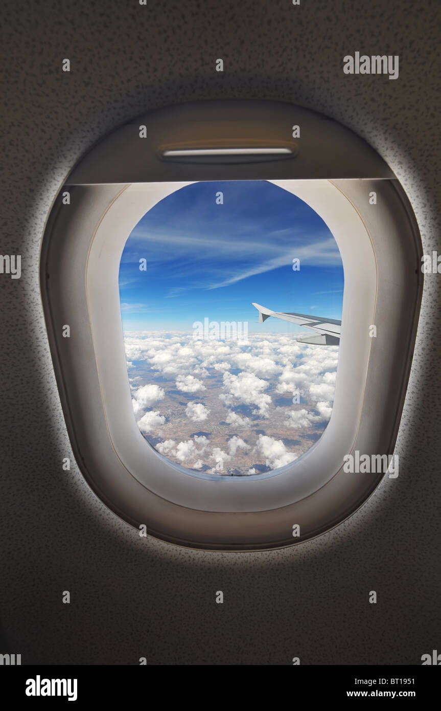 cloudscape seen through an airplane window from the passenger seat - Stock Image