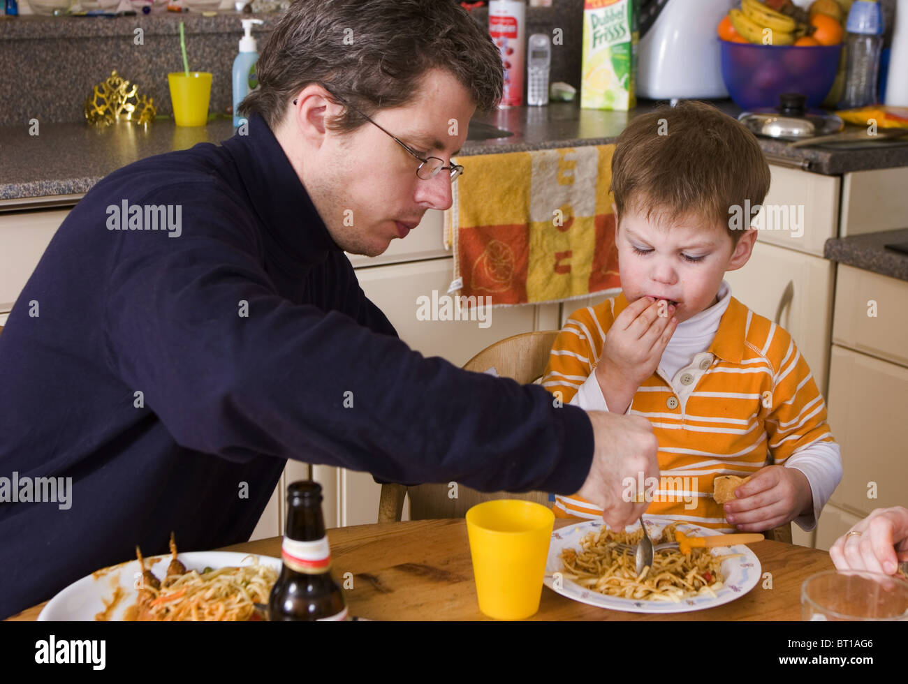 Child with father at dinner table - Stock Image