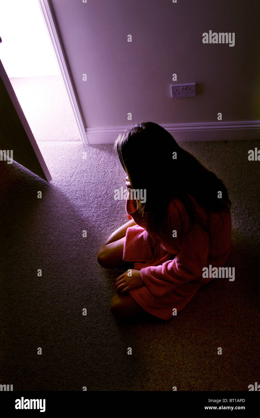 Young girl sitting on floor of a dark room light streaming into the room Stock Photo