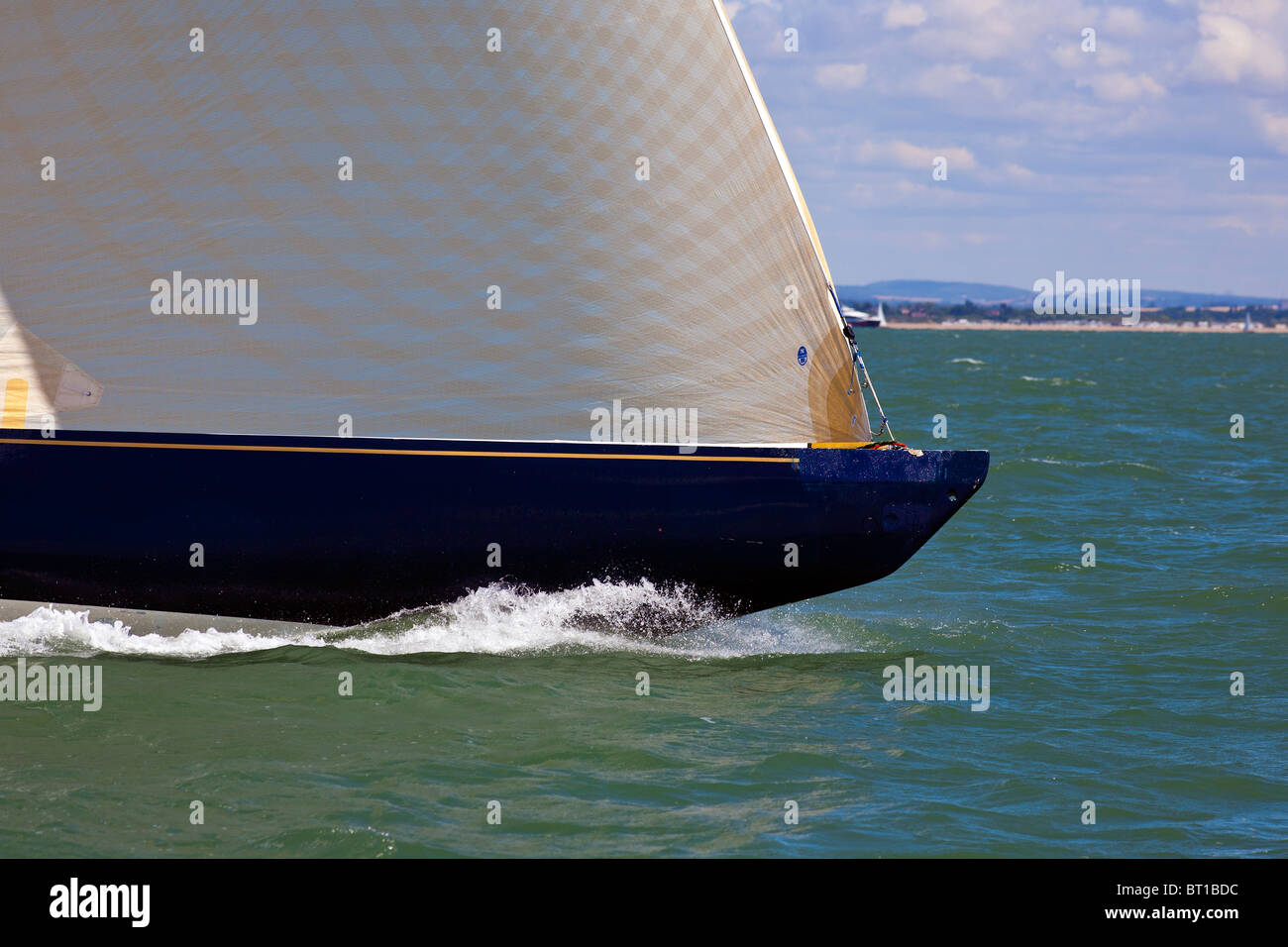 modern racing yacht bow speeding through the water with jib foresail - Stock Image