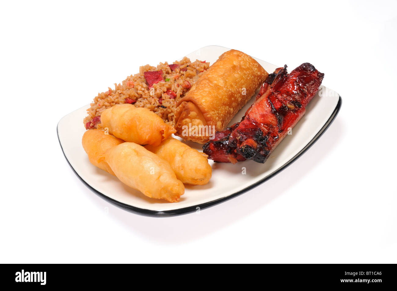 Chinese food dinner of pork fried rice, chicken fingers, spareribs and eggroll on white plate on white background. - Stock Image