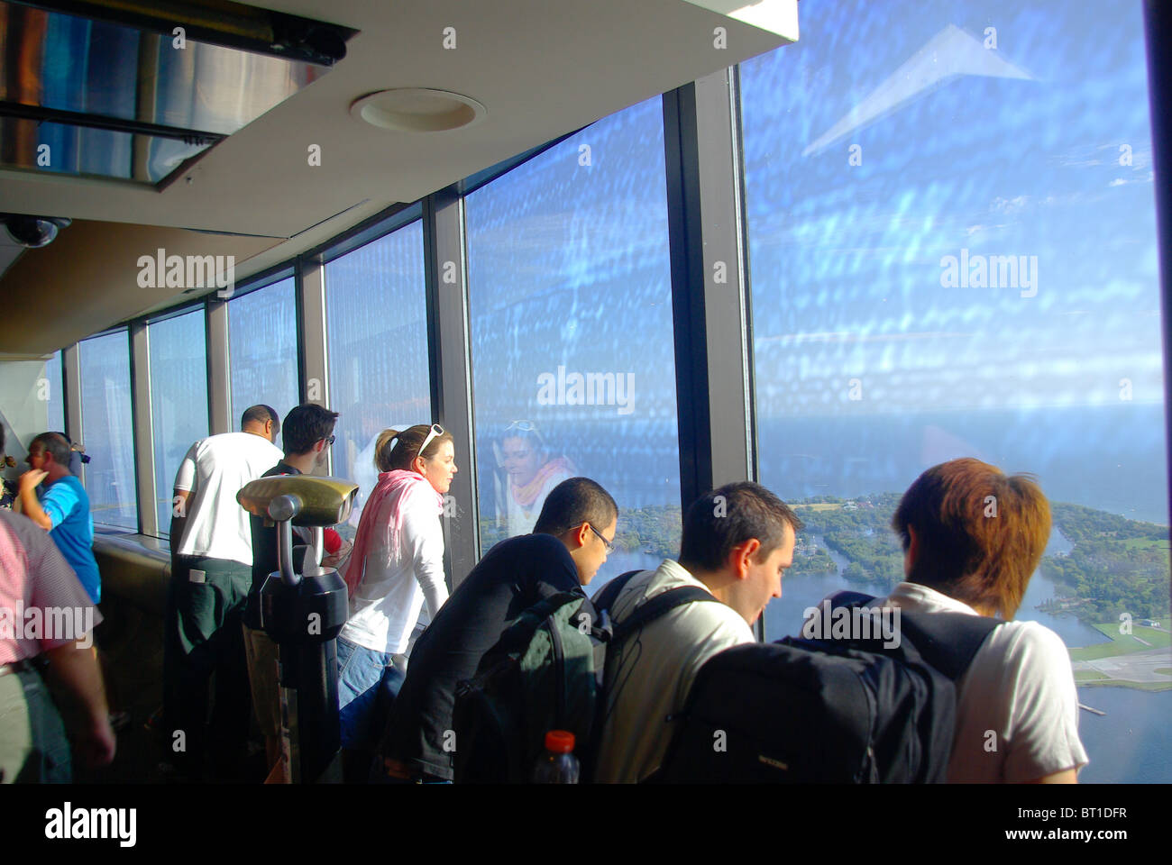 Visitors tourists sightseers look out over the city of Toronto from the top of the CN Tower - Stock Image
