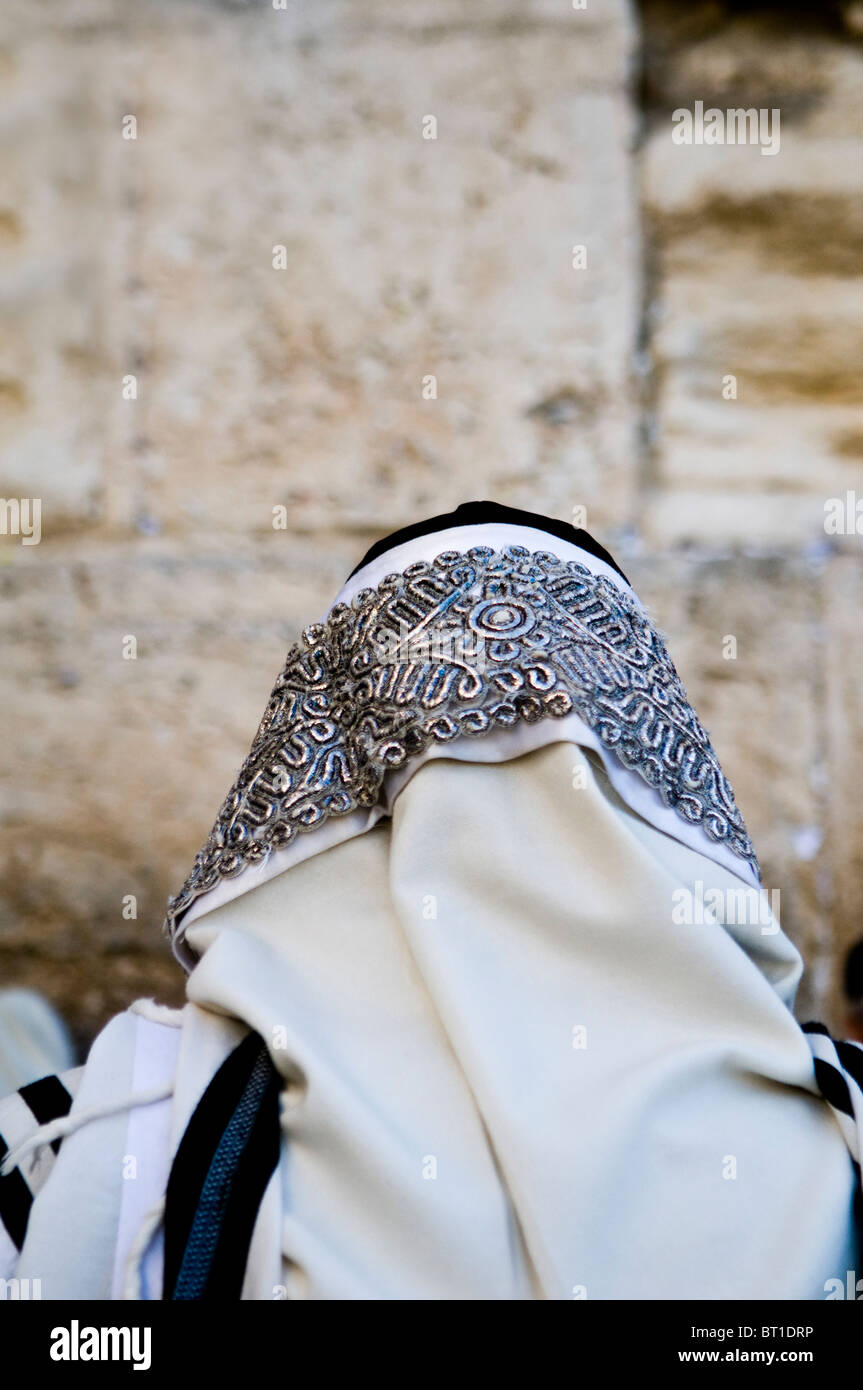 A Jewish man praying at the Wailing wall in the old city of Jerusalem. His head is covered with a Talit. - Stock Image