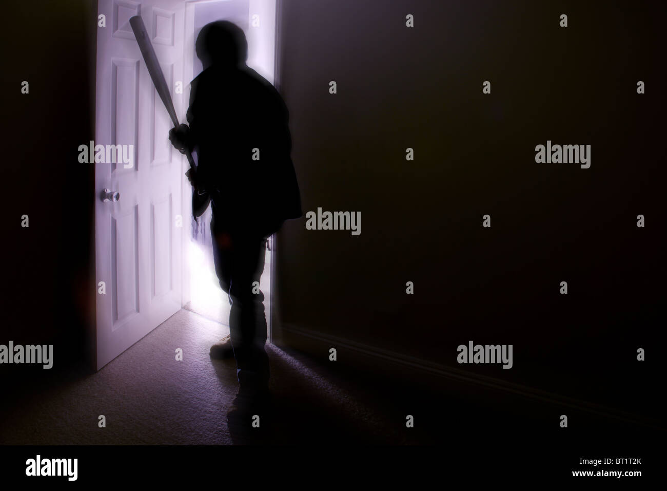 Silhouette of a male with a baseball bat entering a dark room - Stock Image