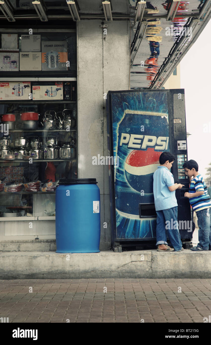 Editorial photo of two boys playing near the Pepsi box - Stock Image
