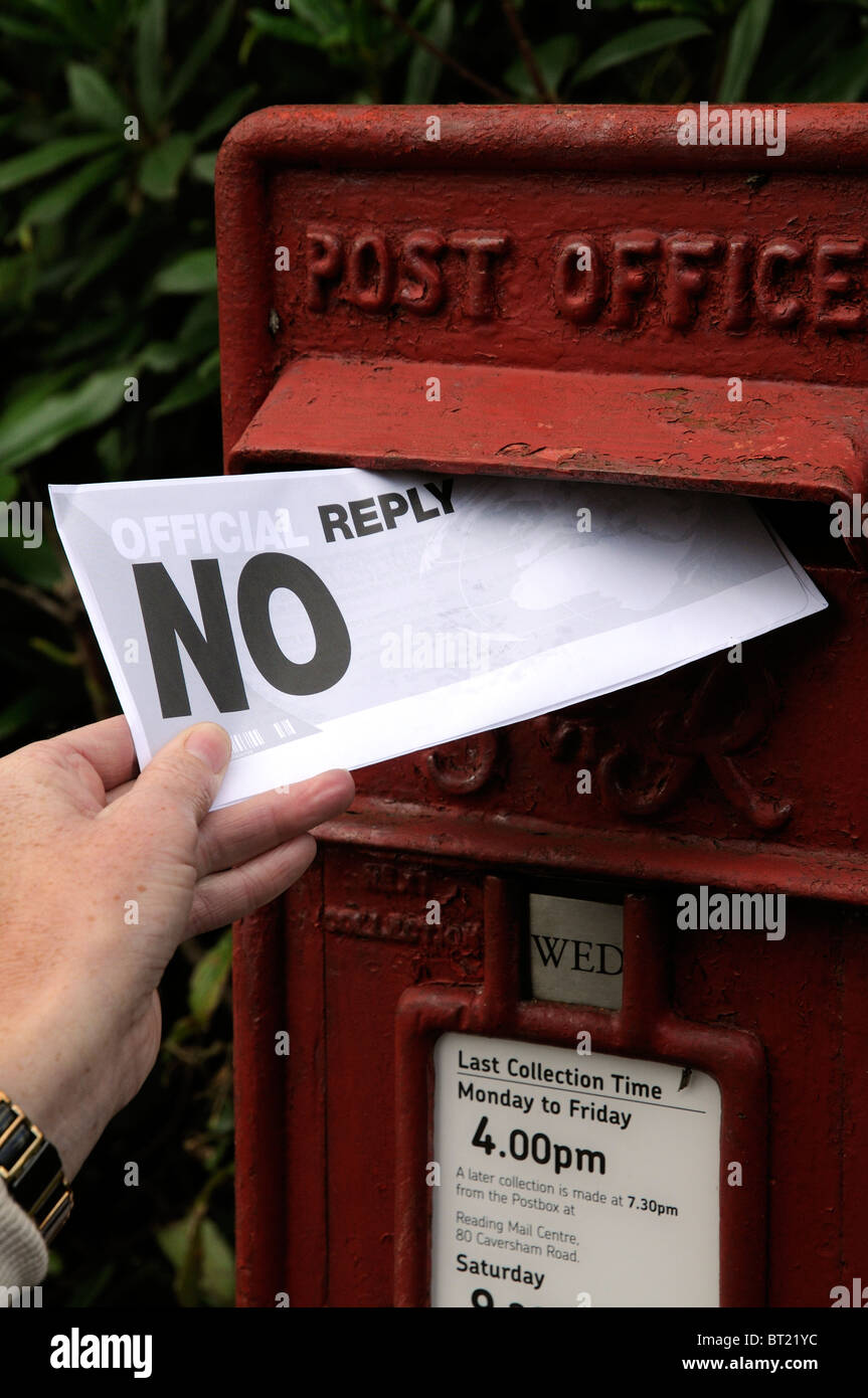 Womans Hand Holding And Posting A Letter Containing The Words No Reply Into A Post Office
