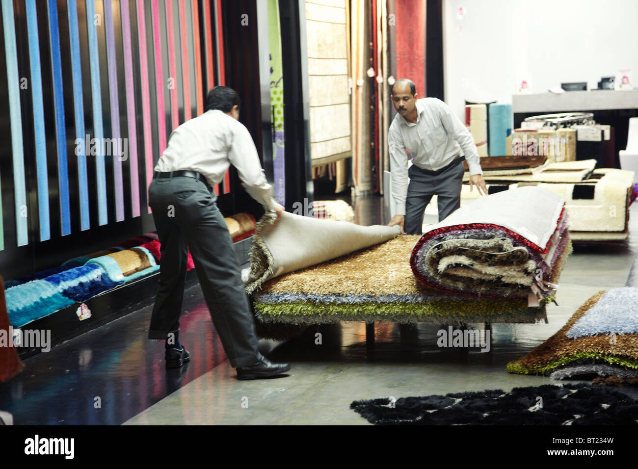 Editorial photo of two men working with carpet in shop - Stock Image