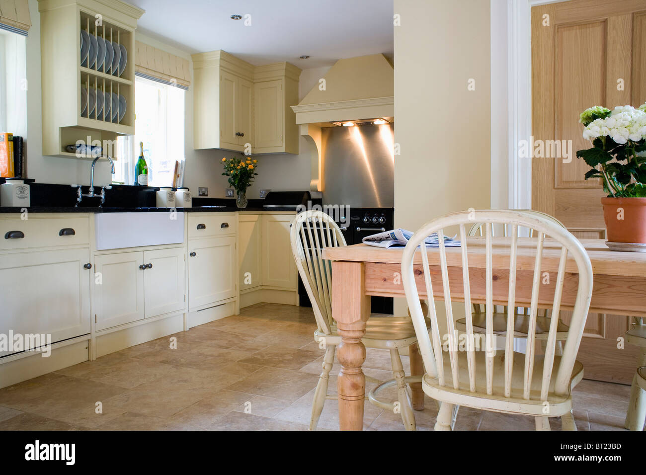 Pale Wood Windsor Chairs And Pine Table In Traditional Country Kitchen With  Cream Fitted Units And Limestone Flooring