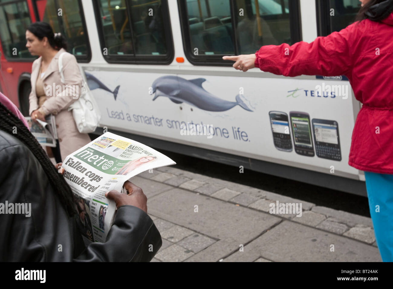 A woman reads a Metro free daily newspaper as she waits for a bus in Ottawa Monday September 27, 2010 Stock Photo