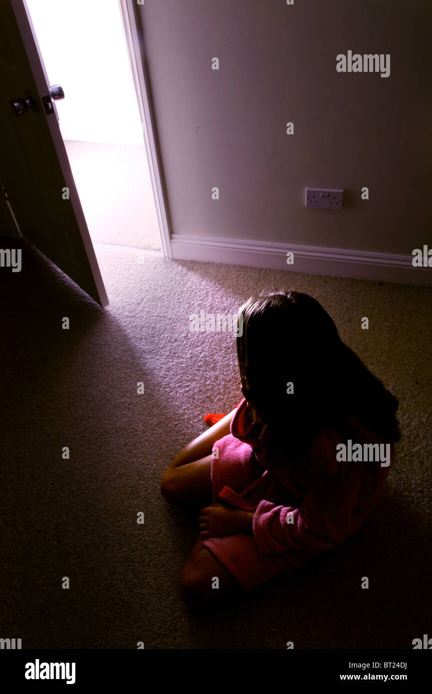 Girl sitting in a dark room, back view looking to an open door where light streams in. - Stock Image