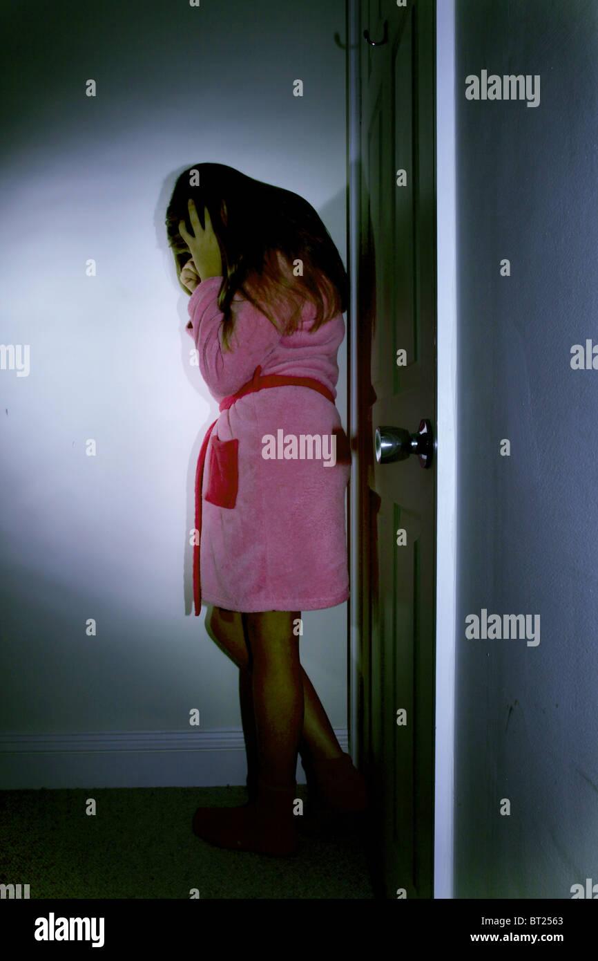 Young girl wearing a dressing gown in her bedroom, head in hands door closed. Stock Photo