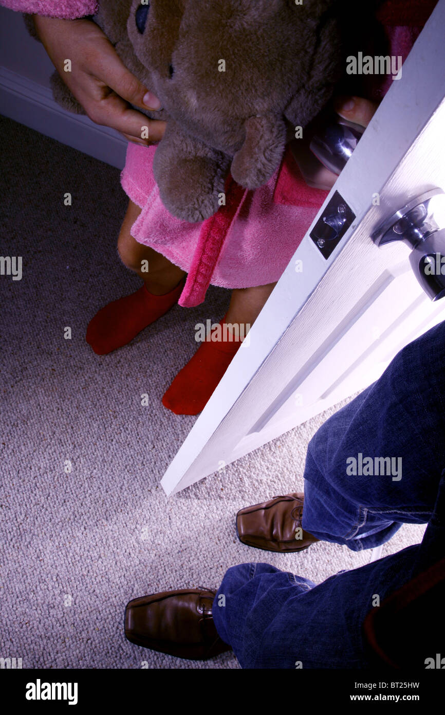 Male feet entering a young girls bedroom while she clutches a teddy bear. No faces shown - Stock Image
