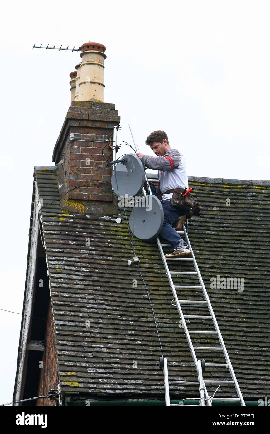 An Aerial and satellite engineer works on a roof top.  Picture by James Boardman - Stock Image