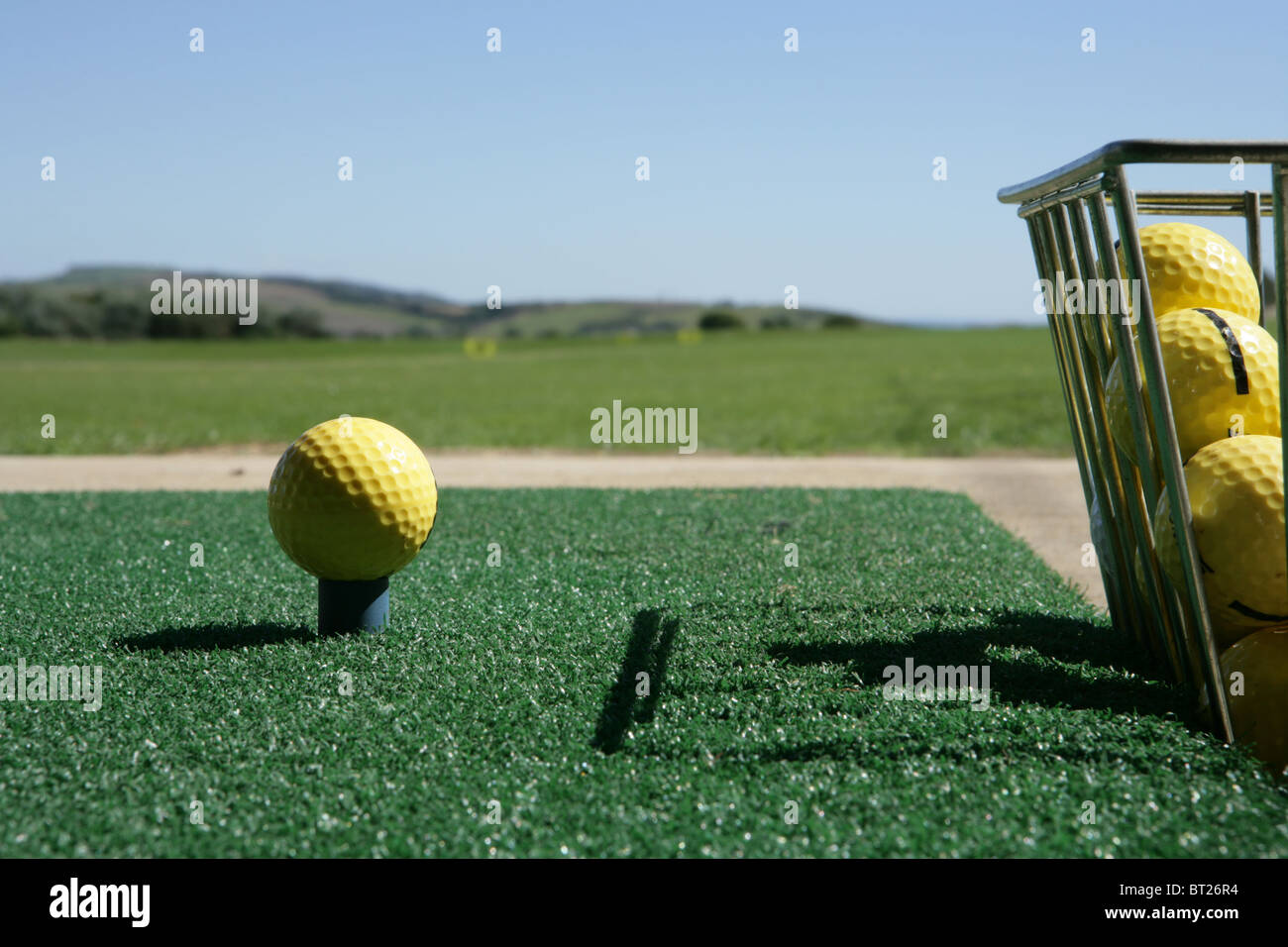 Golf ball and bucket at driving range - Stock Image
