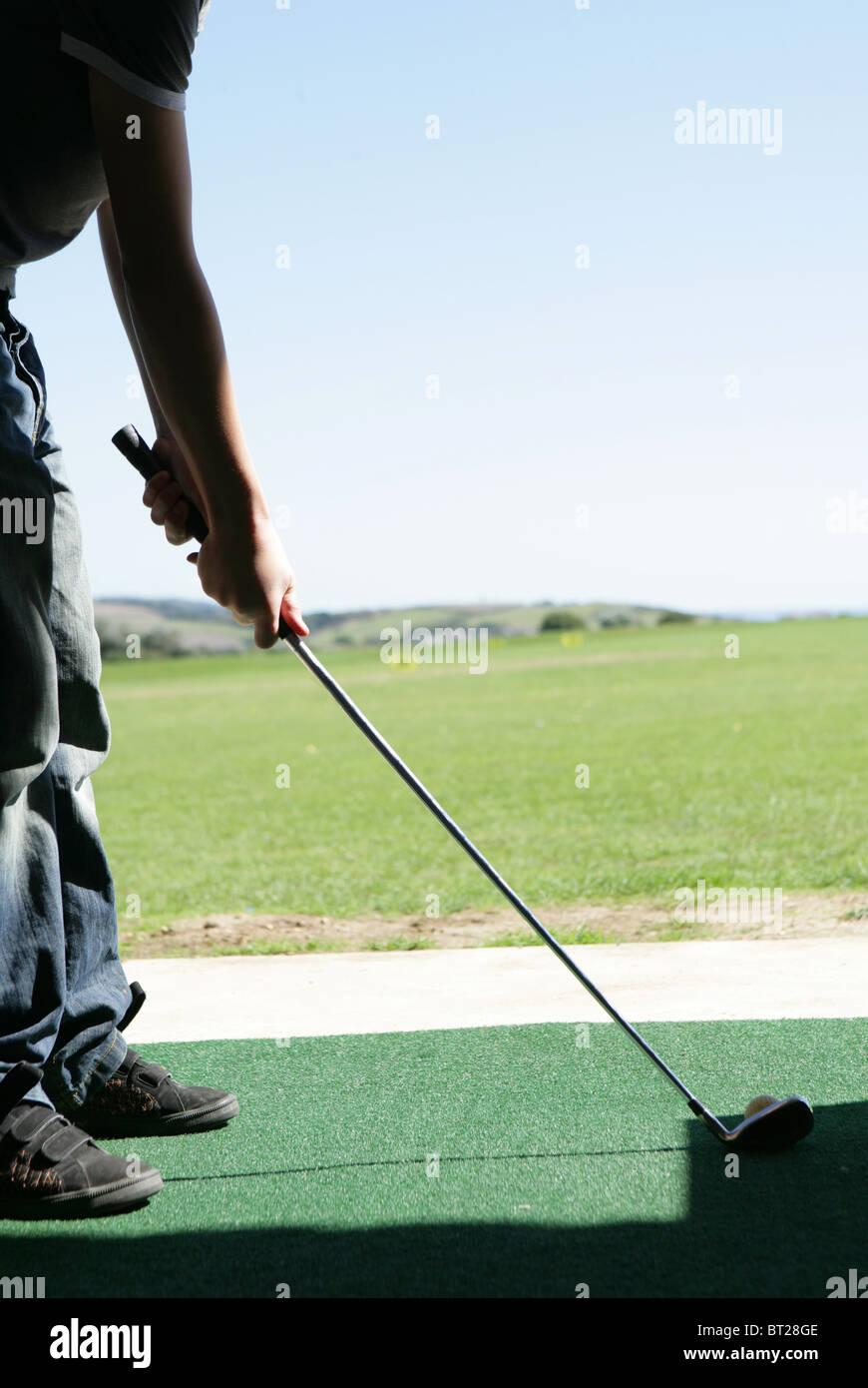 Teenage Golfer at driving range - Stock Image