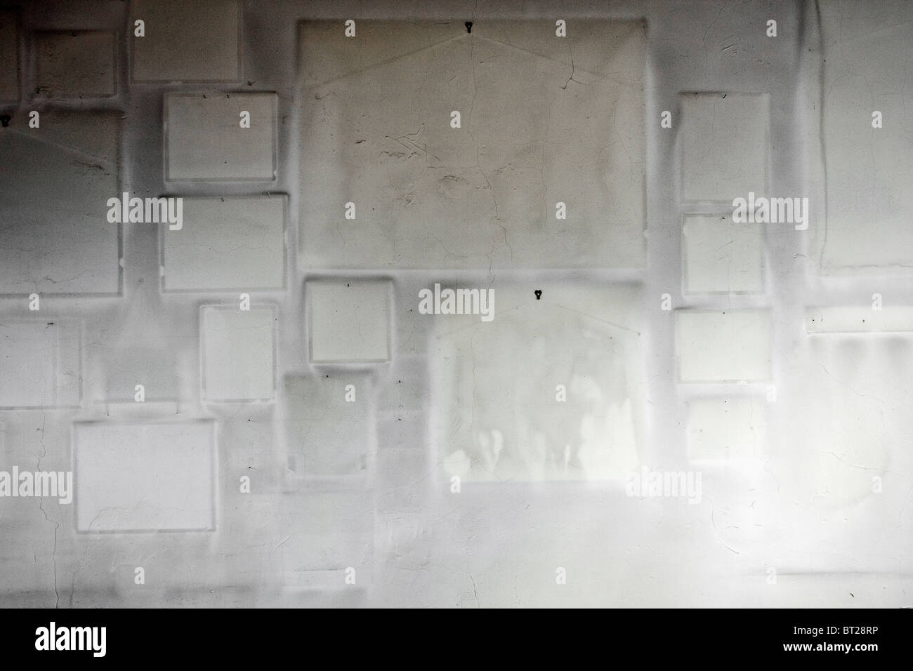 White wall void of hanging art with frame imprints left behind - Stock Image