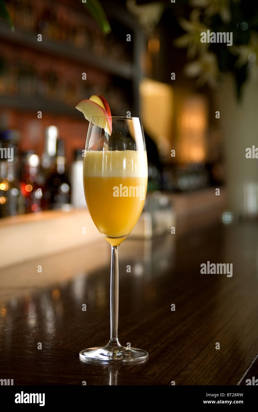 Bellini Champagne Cocktail with apple slice in bar setting. - Stock Image