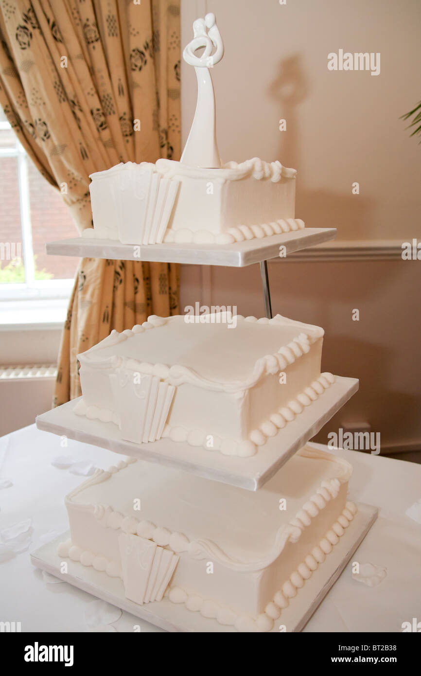 A three tiered wedding cake on display at a wedding reception. The cake is styled in the 1930's Art Deco style. - Stock Image
