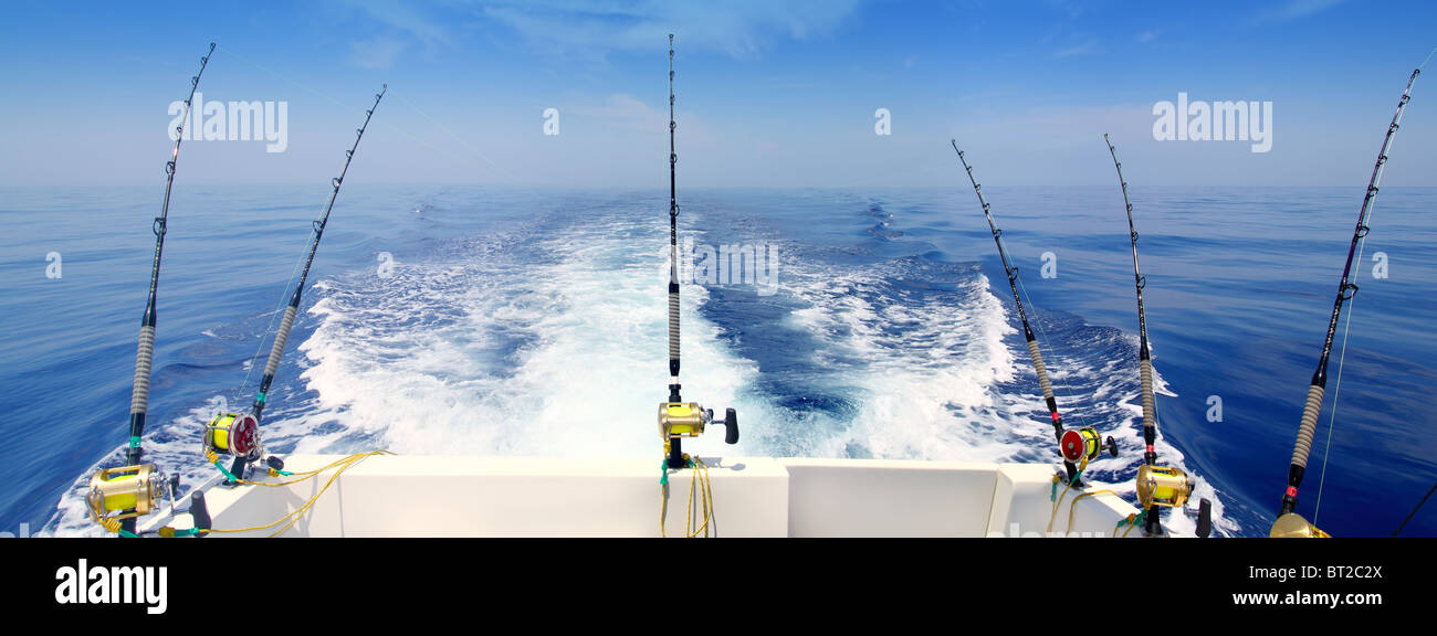 boat fishing trolling panoramic rod and reels blue sea wake - Stock Image