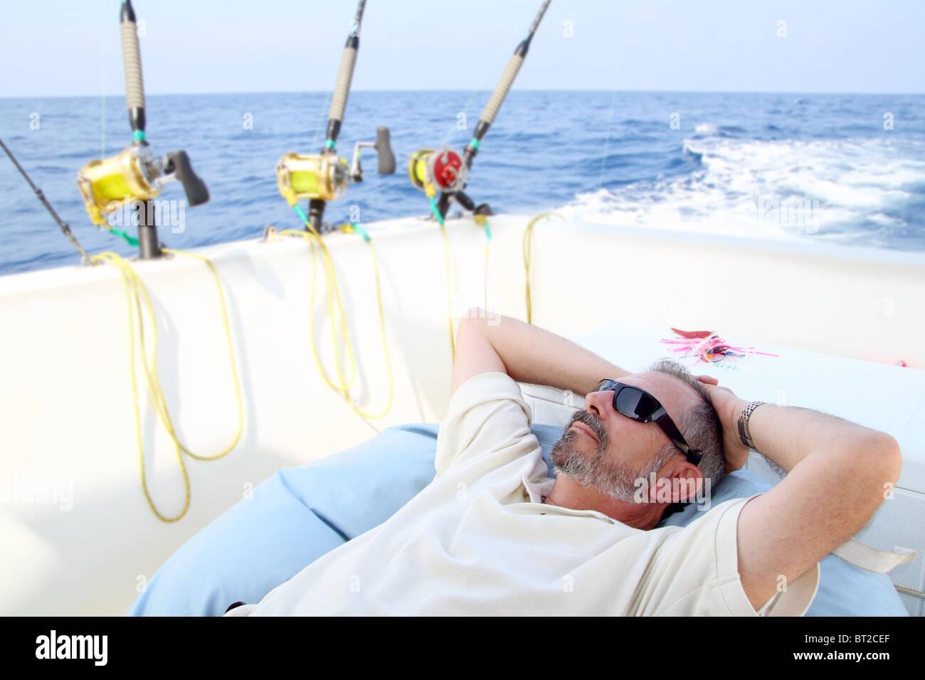Sailor senior fisherman relax on boat fishing deep sea - Stock Image