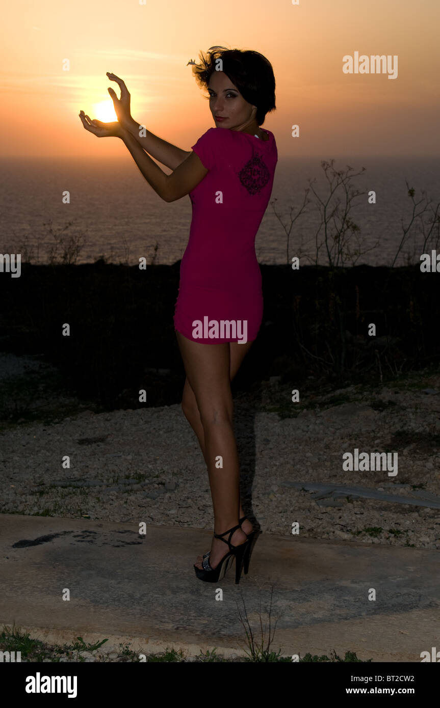 An attractive young woman with short dark hair and wearing a pink mini dress at sunset. - Stock Image