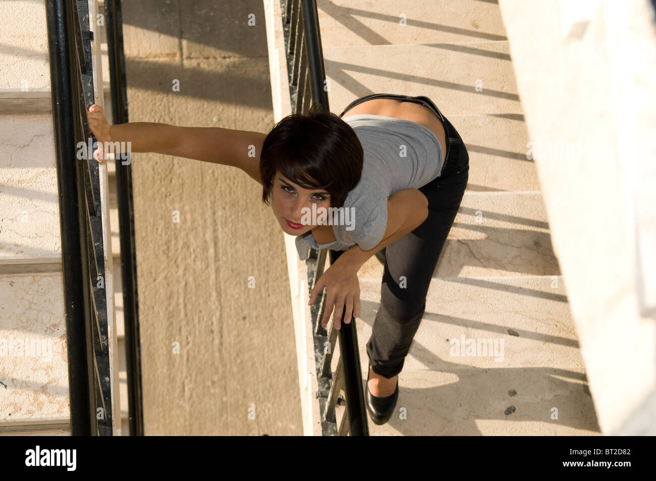 An attractive young woman leans over the banisters of a flight of stairs to look upwards. - Stock Image