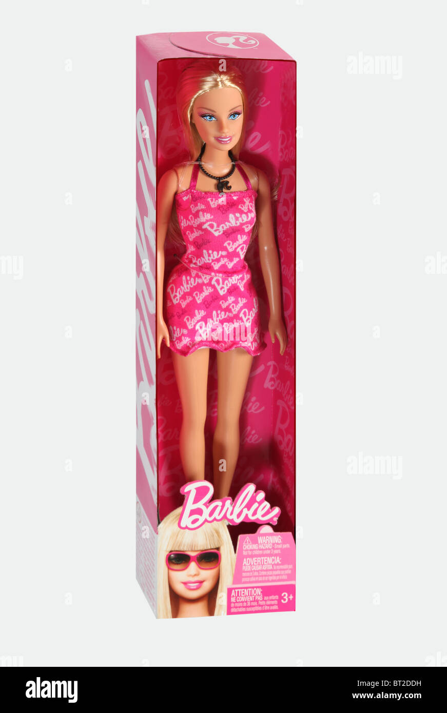 Barbie doll wearing a pink dress and name 'Barbie' across the dress, in original box.. Cut out - Stock Image