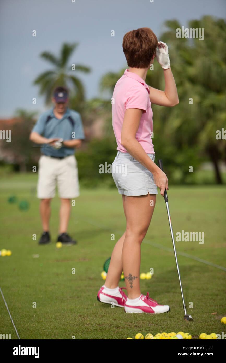 Female golfer on the driving range - Stock Image