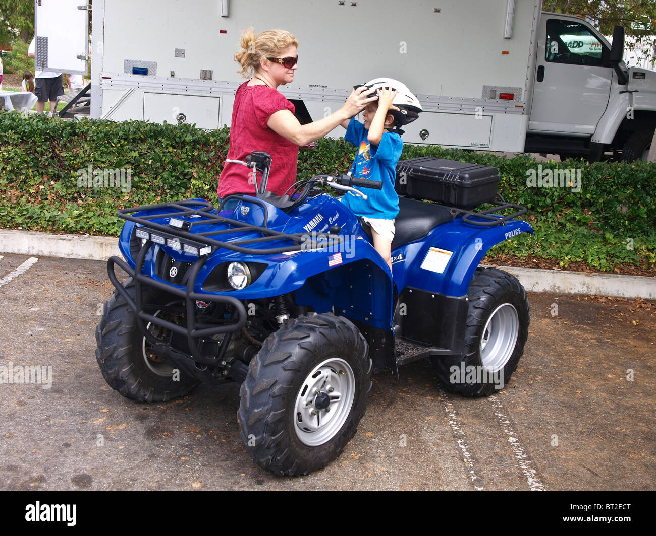 Mom places safety helmet on her little boy astride a four wheeled police ATV at the Redondo Police Dept safety fair. - Stock Image