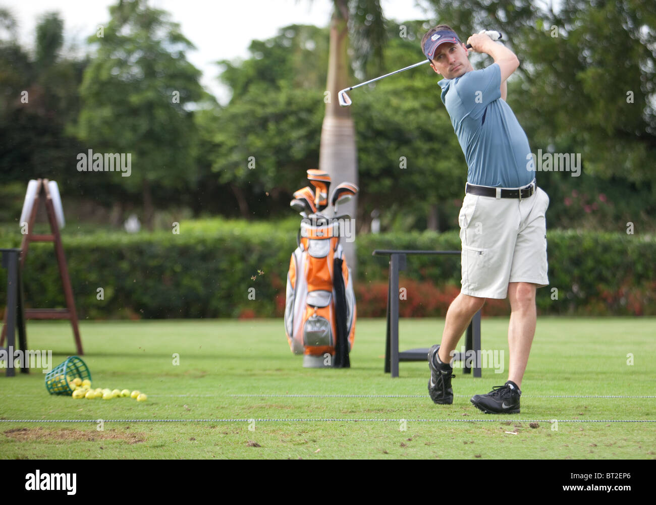 Male golfer hits the ball on the driving range. - Stock Image