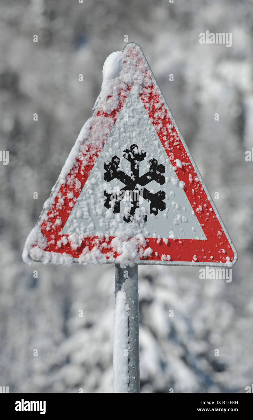 warning sign of snow and ice at road in winter - Stock Image