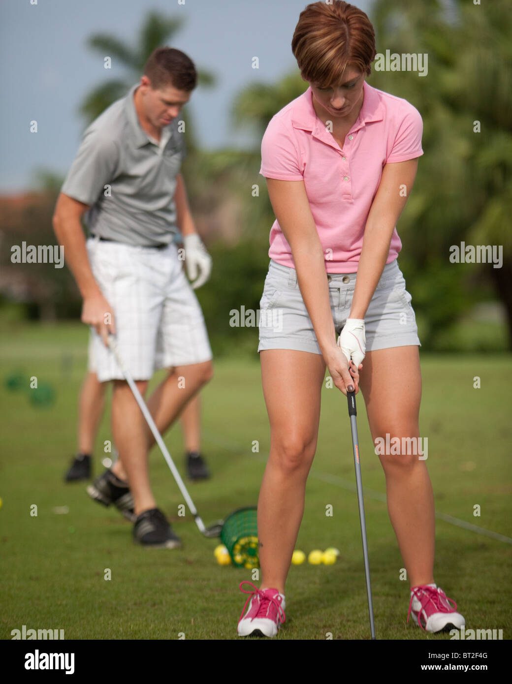 Female golfer on the driving range. A male golfer in the background. - Stock Image