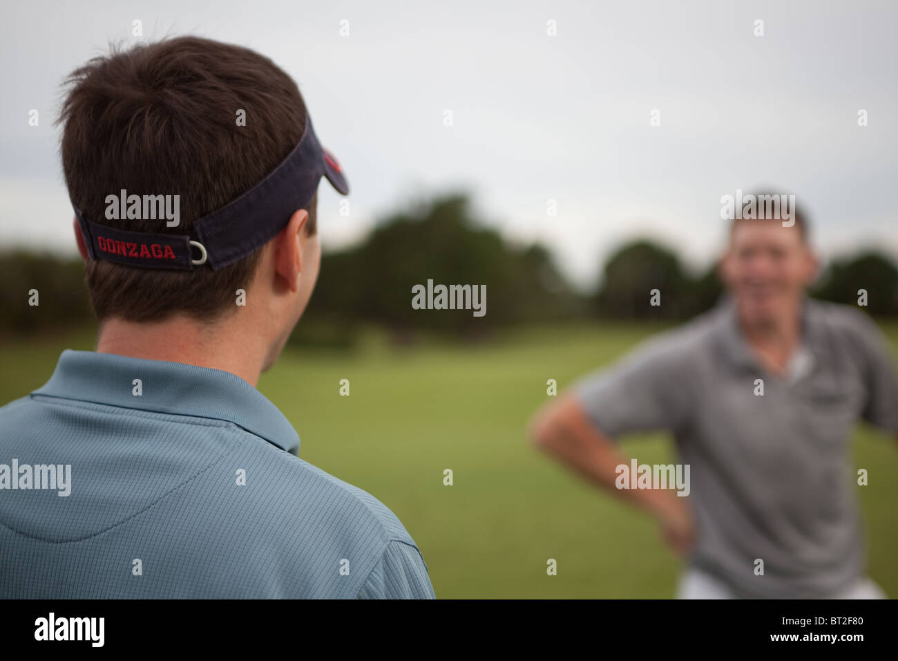 Two golfers tease each other. - Stock Image