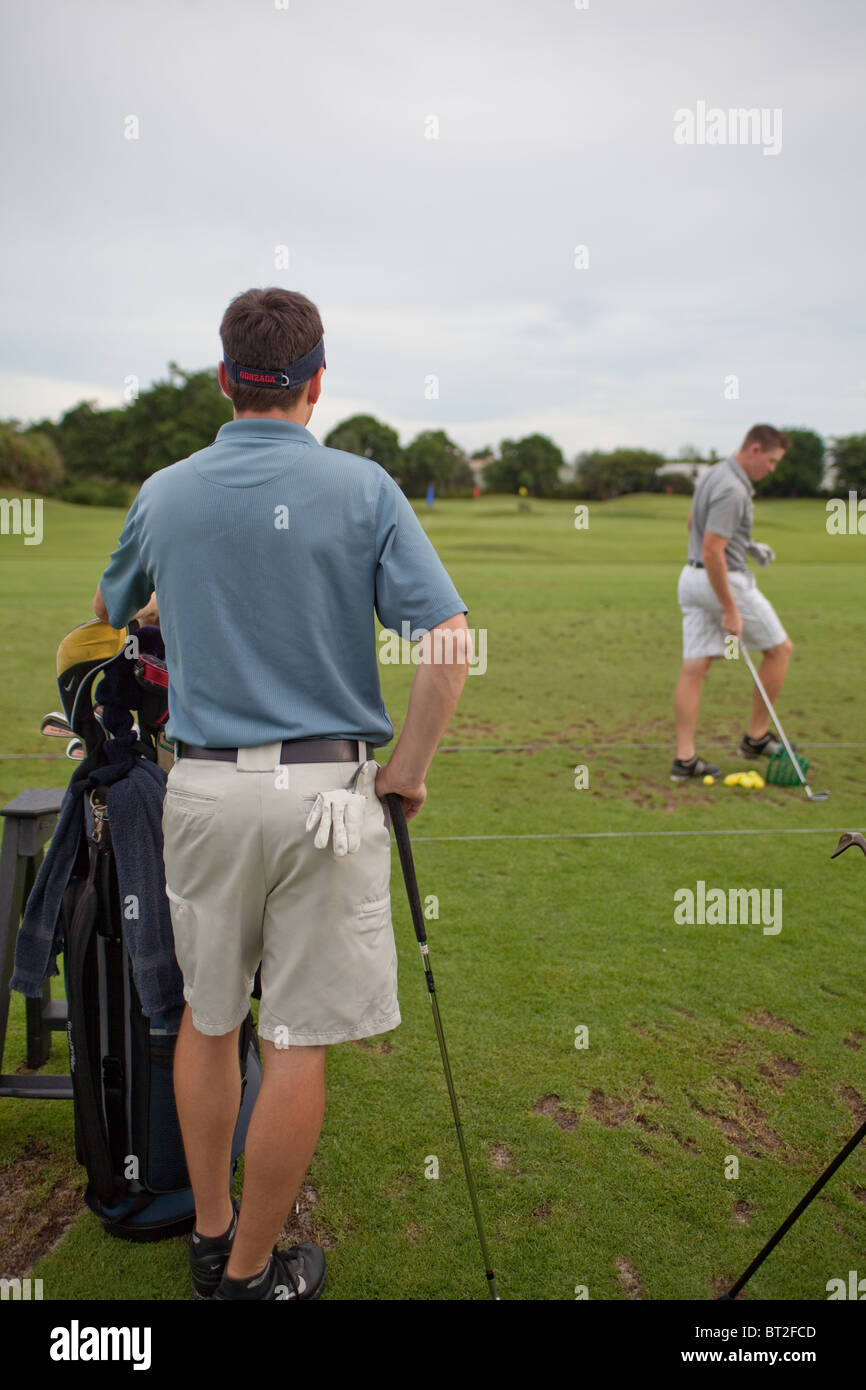 Two male golfers on the driving range. - Stock Image
