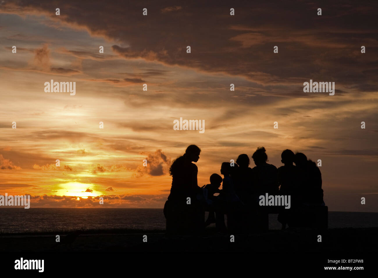 Silhouettes of Sri Lankans along the ramparts of Galle Fort at sunset - Stock Image